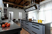Modern island counter in kitchen of renovated country house with rustic wood-beamed ceiling