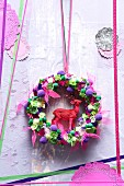Hand-made door wreath with stag figurine and pink ribbon