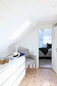 Modernes Sideboard mit Schubladen unter Dachschräge vor offener Schlafzimmertür