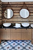 Custom washstand with twin white washbasins below round mirrors hung on rustic log-cabin wall