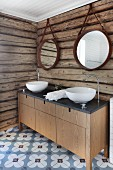 Custom washstand with twin white washbasins against rustic log-cabin wall and cement floor tiles with floral pattern