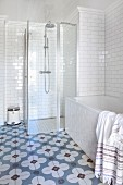 Bathtub, glazed shower cabinet, white-tiled walls and cement floor tiles with floral pattern in bathroom