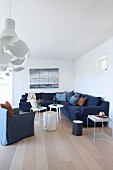 Living room with white wood cladding, dark blue corner couch and armchair around white side tables