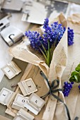 Grape hyacinths wrapped in vintage paper amongst small alphabetical labels