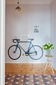 Blaues Fahrrad hängt an der Wand im Flur, Blumen auf einem Hocker