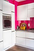 Moderne weiße Küche mit pinker Wand