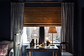 Table lamp on antique desk in front of window with bamboo roller blind and matching blue and white patterned curtains, armchair and chair seat