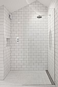White-tiled shower area with rainfall shower in attic bathroom