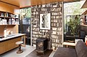 Home Office mit Schwedenofen vor Fototapete mit Bücherwandmotiv in modernem Anbau mit raumhoher Verglasung