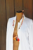Necklace made from various crocheted cords, wooden beads and tassels hanging on tailors' dummy wearing white blouse