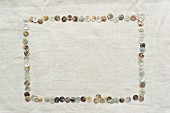 Frame made from mother-of-pearl buttons laid on linen cloth