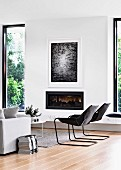 Lounge area with cantilever chair next to gas fireplace and window elements with black frames
