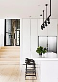 White kitchen island and bar stool under light rail with black spotlights in open kitchen
