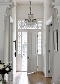 Elegant, traditional house entrance with half-open front door and leaded glass window elements