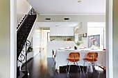 Classic wooden chairs at a set dining table in front of the kitchen area, to the side of the stairs