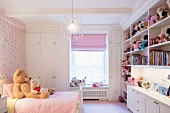 Collection of soft toys on fitted shelves in pink child's bedroom