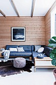 Corner sofa with blue upholstery in front of rustic wooden wall in corner of living room