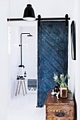 Bathroom with blue vintage door leaf as sliding element and rain shower