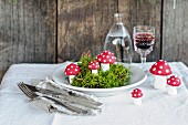 Moss and hand-made toadstool ornaments on plate