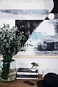 Blätterzweige in Glasvase, Bücherstapel und schwarzer Hut vor Wand mit modernem Bild