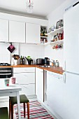 Corner of white kitchen with wooden worksurface, bracket shelves and wall cabinets
