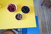 Drei Schälchen mit Erdbeeren, Kirschen und Schokokeksen auf gelber Tischplatte, darunter blauer Tritthocker