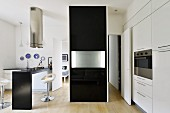 Black partition with folded-up table top in minimalist designer kitchen