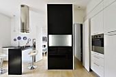 Schwarzer Raumteiler mit eingeklappter Tischplatte in minimalistischer Designerküche