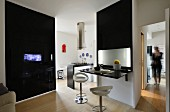 Black partition with integrated TV and partition with fold-up glossy table