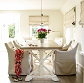 Rustic dining room with pale wooden table and chairs with loose covers