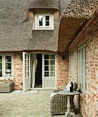 Terrasse mit Korbmöbeln vor einem Backsteinhaus mit Reetdach
