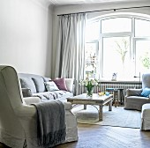 Sofa set, coffee table and arched window with curtains in traditional interior