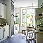 White fitted kitchen, kitchen table and high chair in front of open French windows