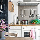 Cooking utensils hung on wall below extractor hood on grey-tiled splashback in country-house-style kitchen