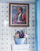 Framed oil painting of girl on traditional blue and white wall tiles with border and flower arrangement in pot