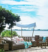Rattan chaise under awning on wooden terrace with view of river Elbe
