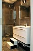 Geflieste Badezimmerecke mit schwarz-weißem Trittschemel vor Waschtischunterschrank