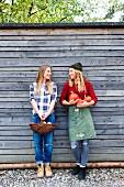 Junge Frauen mit frischen Äpfeln und Kürbissen aus dem Garten an einer grauen Holzwand stehend