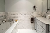 Bathroom with marble wall tiles, washstand counter and bathtub cladding