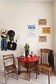 Folding table, two wooden chairs, vintage posters on wall and collection of hats on coat pegs