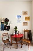 Klapptisch und zwei Holzstühlen vor Wand mit Vintage Postern und Garderobe mit Hutsammlung