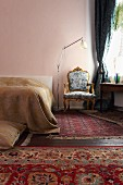 Baroque armchair and various rugs in bedroom