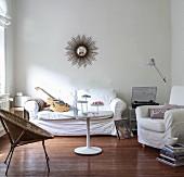 Wohnbereich mit Korbsessel, weiss bezogenem Hussensofa und Sessel um runden Couchtisch