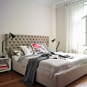 Box-spring bed with beige, button-tufted headboard next to black table lamps on bedside tables