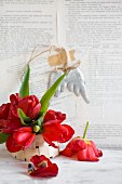 Red tulips in chip-wood basket against wall papered with book pages