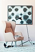 Pink wing chair and black floor lamp in front of a modern picture on a pink wall
