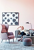 Woman on gray sofa next to pink wing chair and pouf