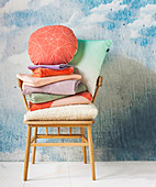 Retro armchair with stack of laundry and pillows