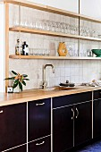 Kitchenette with black fronts and shelves on wall with glasses