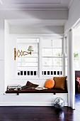 Custom-made white bench with brown seat upholstery in front of rung interior window